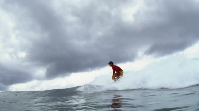 water level shot of surfer jumping up onto his board - pacific islander male stock videos & royalty-free footage