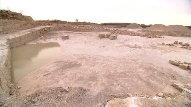 stockvideo's en b-roll-footage met water lies in low spots in a limestone quarry. - steengroeve
