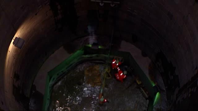 london ring main breakthrough; england: north east london: islington: ext water engineers, wearing hard hats and fluorescent jackets, looking down... - herunterlassen stock-videos und b-roll-filmmaterial