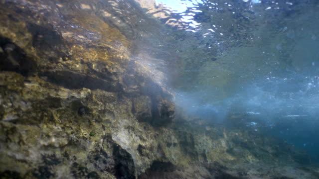 stockvideo's en b-roll-footage met massa's van het water weerspiegeld door onderwater kliffen, poreuze rotsenstranden en kleine grotten. de wateroppervlakte uit de seabottom. turkoois water en de stralen van de zon. - poreus
