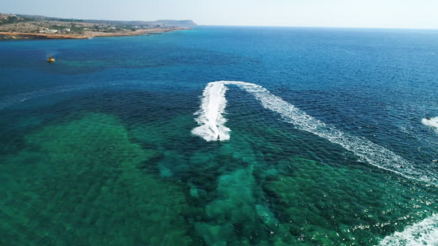 water motorcycle impetuously moving forward in the mediterranean sea. nissi beach, ayia napa, cyprus.  aerial drone shot. - republic of cyprus stock videos and b-roll footage