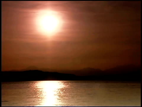 water moves along in the puget sound as the sun starts to set over the mountains. - nordpazifik stock-videos und b-roll-filmmaterial