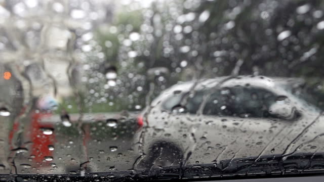 Water of Rain flowing down on the Windshield Car.