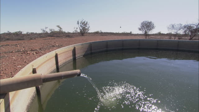 MS Water pouring from pipe into water trough, helicopter landing in background, Tinnenburra Sheep Station, Queensland, Australia