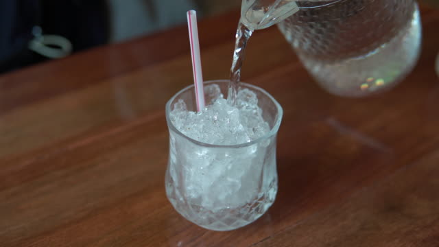 water pouring into drinking glass with ice. - jug stock videos & royalty-free footage