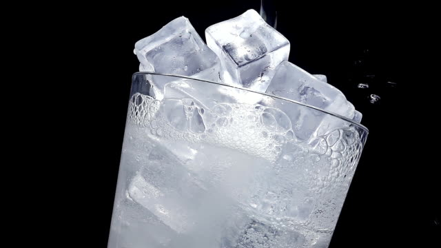 water pouring into glass of ice at slow motion - filling stock videos & royalty-free footage