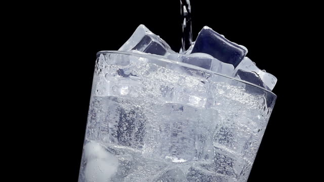 Pouring water into glass of ice at slow motion