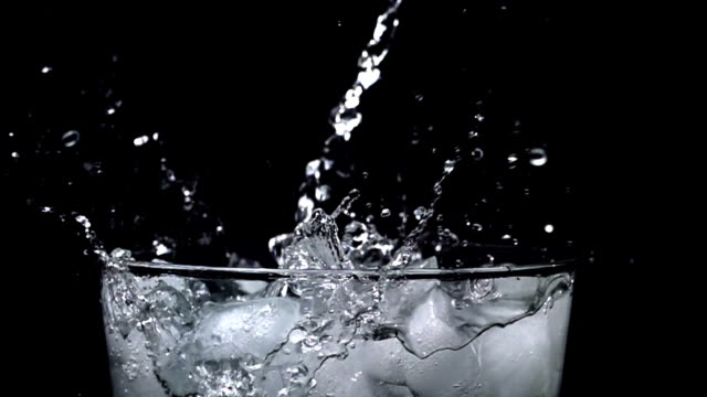 water pouring into glass of ice with splashes at slow motion on black background - thirsty stock videos & royalty-free footage