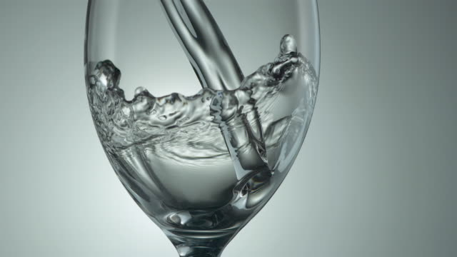 water pours into a wine glass in slow motion. - グラス点の映像素材/bロール