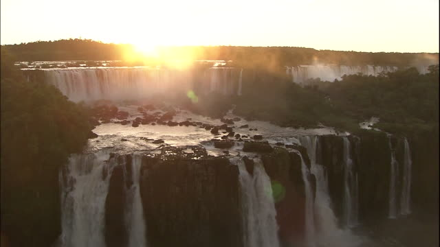 Water pours over Iguazu Falls at sunset, border of Brazil and Argentina