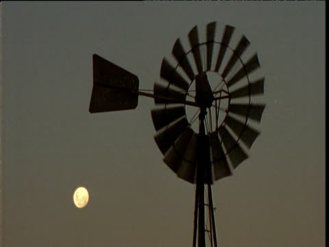 water pump windmill spins with moon behind in outback, northern territory, australia - drought stock videos & royalty-free footage