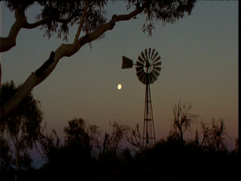 water pump windmill spins with moon behind in outback, northern territory, australia - mill stock videos & royalty-free footage