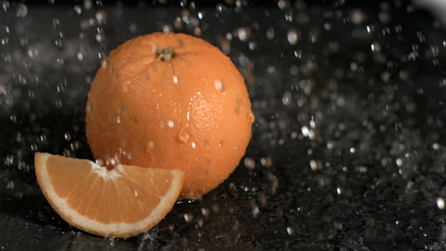 vídeos de stock e filmes b-roll de water raining on oranges in super slow motion - laranja