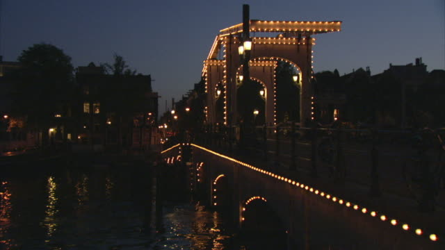 MS ZO WS Water reflecting illuminated Magere Brug at night on Amstel River / Amsterdam, Netherlands