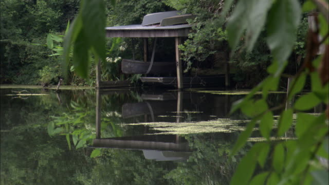 Water reflects boats in a boathouse and the foliage surrounding them.