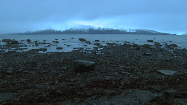 water ripples onto a stony beach in alaska. - tide stock videos & royalty-free footage