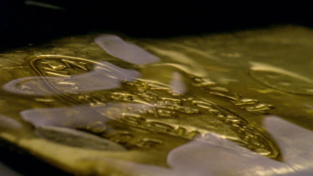 water ripples over a gold ingot. - ingot stock videos & royalty-free footage