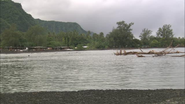 vídeos de stock e filmes b-roll de water ripples up on the tahitian shoreline. - territórios ultramarinos franceses