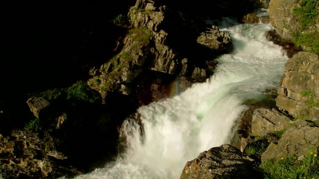 vídeos de stock, filmes e b-roll de water rushes down a cliff from grinnell glacier. - neve derretida