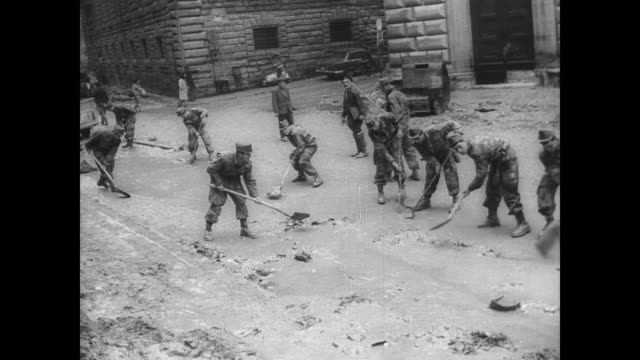 water rushes down the arno river in the aftermath of a devastating flood / mud and rubble on the streets of florence / soldiers use brooms to brush... - 1966 stock-videos und b-roll-filmmaterial