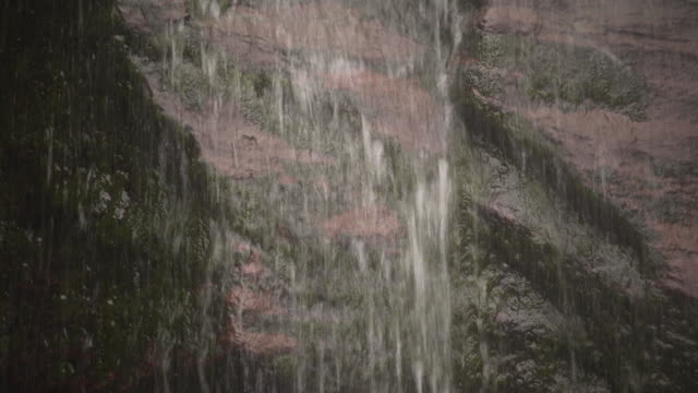 Water rushes over mossy rocks of the Kaaterskill Falls in the Catskill Mountains, New York State, USA.