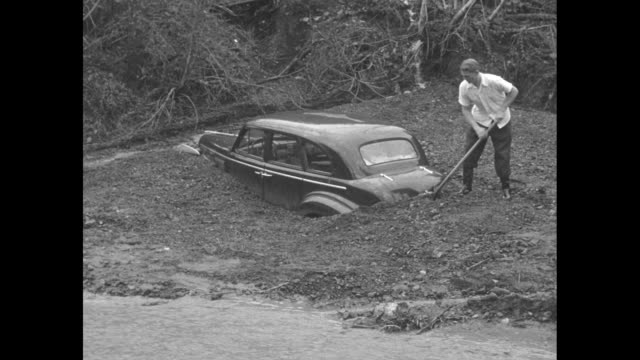 water rushes past car stuck up to its fender in mud as men work to free it / man and boy look at car submerged in deep mud next to house on hill /... - feststecken stock-videos und b-roll-filmmaterial