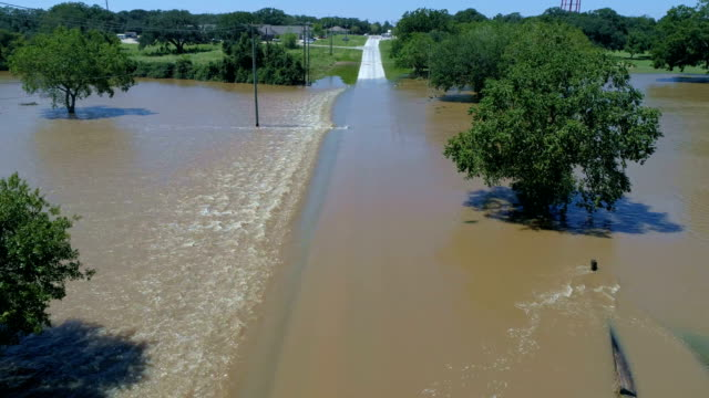 Water Rushing across low water crossing after Hurricane Harvey Floods Columbus , Texas during massive rainfall and flooding in small Texas town aerial drone view
