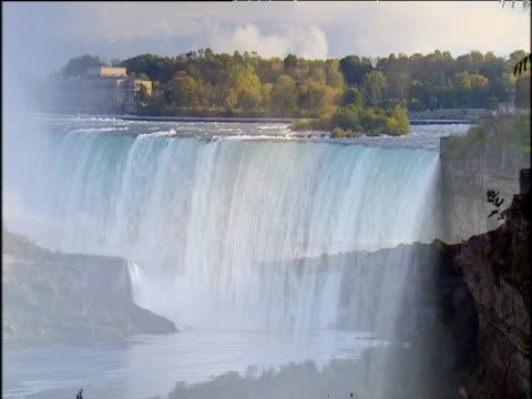 water rushing over niagara falls under blue sky - niagara falls stock videos & royalty-free footage