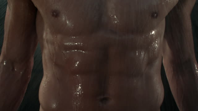 water showers on a muscular man's abs and torso. - torso stock videos & royalty-free footage