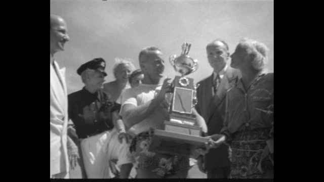 Water skiers Bruce Parker Evie Wolford with trophy // title card Olympic test NCAA track meet superimposed on racers starting dash race