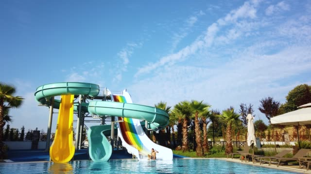 water sliding at water park, swimming pool at holiday resort - water slide stock videos & royalty-free footage