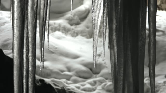 water slowly drips from melting icicles in a cave. - icicle stock videos and b-roll footage