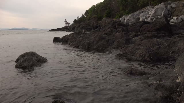 Water Slowly Lapping Against Rocky Shoreline with Distant Lighthouse
