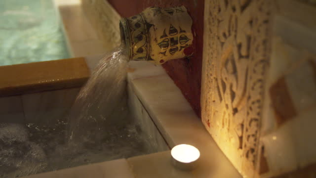 CU water spigot emptying into marble basin in traditional Arab baths