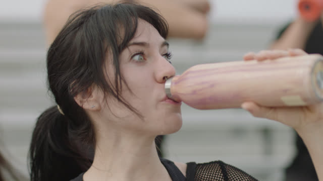 slo mo. water spills down a fit woman's face while a group of athletic woman prepare to exercise together - water bottle stock videos & royalty-free footage