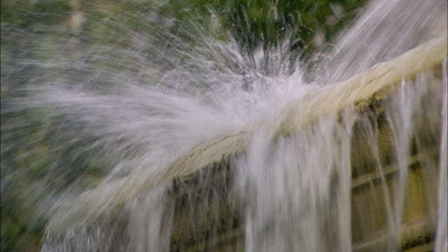 water splashes on a stone ledge in a fountain. - fountain stock videos & royalty-free footage