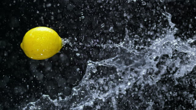 SLO MO Water splashing a lemon in the air