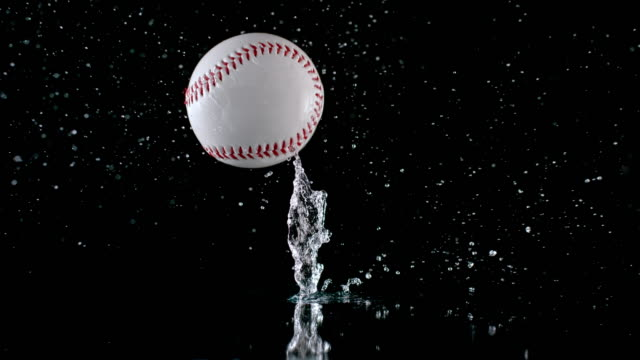 slo mo ld water splashing as a baseball hits the wet surface - rimbalzare video stock e b–roll