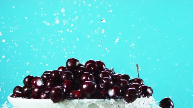vídeos y material grabado en eventos de stock de water splattering on cherries in a plate - gota de agua salpicando