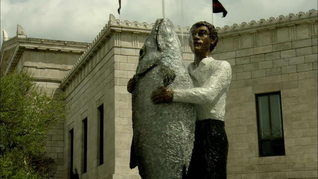 vídeos de stock e filmes b-roll de water spouts from a statue of a man holding a fish. - aquário john g shedd
