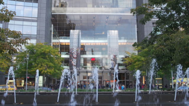 ms water spouts from columbus circle fountain in fg cars moving around traffic circle and glass facade entrance of time warner center in bg - time warner center stock videos & royalty-free footage