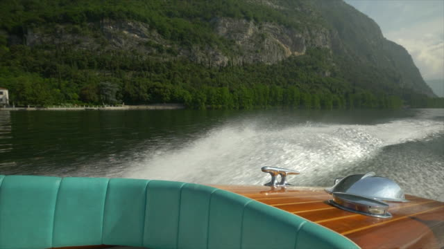Water spray comes from a classic luxury wooden runabout boat on an Italian lake. - Slow Motion