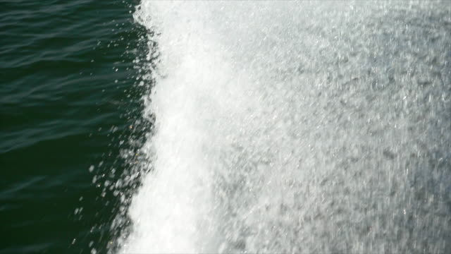 water spray comes from a classic luxury wooden runabout boat on an italian lake. - slow motion - motorboat stock videos & royalty-free footage