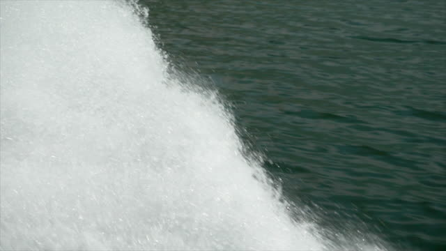 water spray comes from a classic luxury wooden runabout boat on an italian lake. - slow motion - motorboot stock-videos und b-roll-filmmaterial
