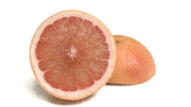 Water sprayed on grapefruit in super slow motion