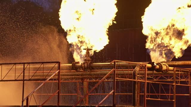 4k uhd spruzzatura di acqua dal pompiere per combattere con esplosione di perdite di oleodotti ed esplosione su piattaforma petrolifera e stazione di gas naturale. concetto di diaster assicurativo e di sicurezza. - incendio video stock e b–roll
