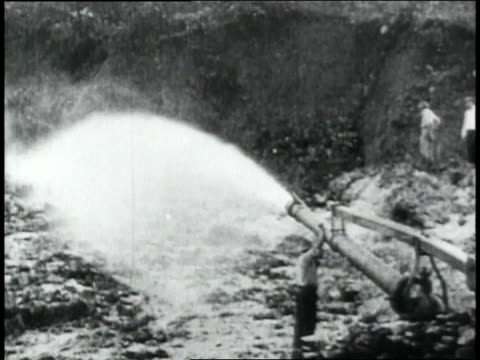 montage water spraying out of a pipe during panama canal excavation a tree falling / republic of panama - 1906 stock-videos und b-roll-filmmaterial