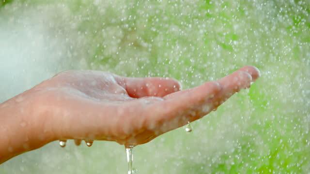 vídeos de stock, filmes e b-roll de super slo mo água pulverizando sobre a mão de mulher aberta - refresco