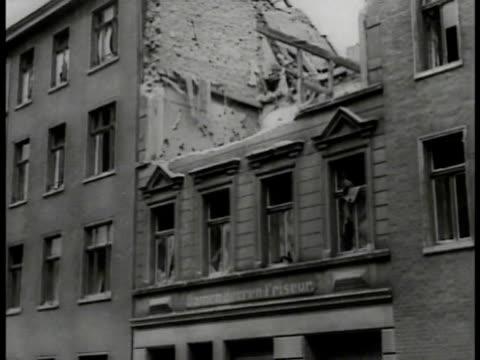 vidéos et rushes de water spraying rooftop la destroyed building vs german workers clearing rubble debris la bombed building furniture on street crowd of children... - 1941
