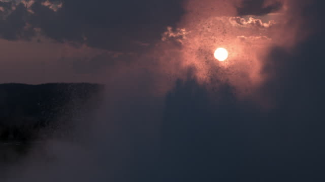 Water sprays into the air as geyser erupts in front of setting sun.